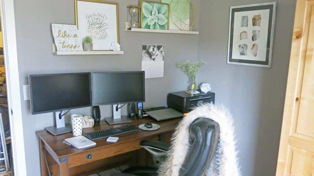 Art on shelves above computer, personalized calendar, computer with dual monitors, planter on the top of the printer, industrial table and fur throw on the office chair