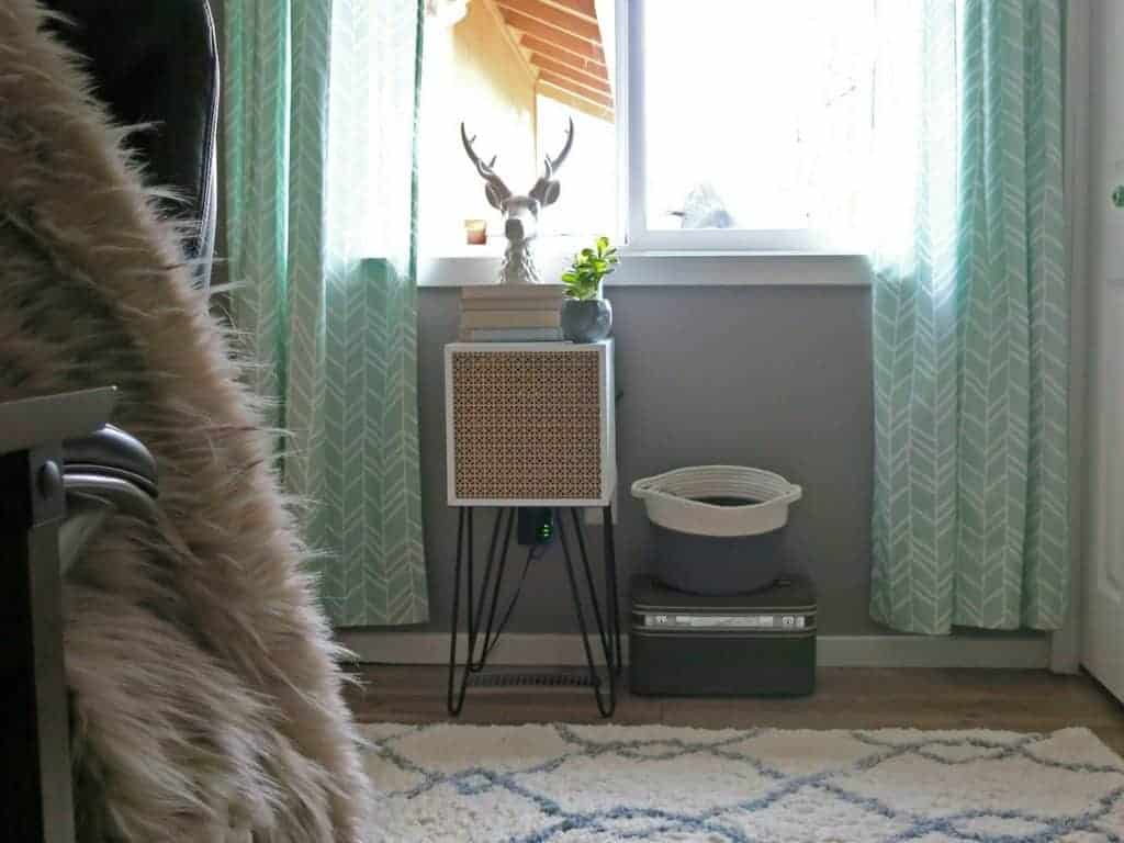Repurposed Mid-Century modern side table with hair pin legs, white stag head decor, bin storage, vintage suitcase and mint curtains.