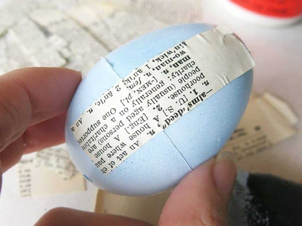 Use mod podge to attach the vintage book pages to the plastic Easter egg
