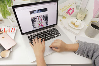Woman's hands typing on a Apple laptop with girly desk items surrounding her