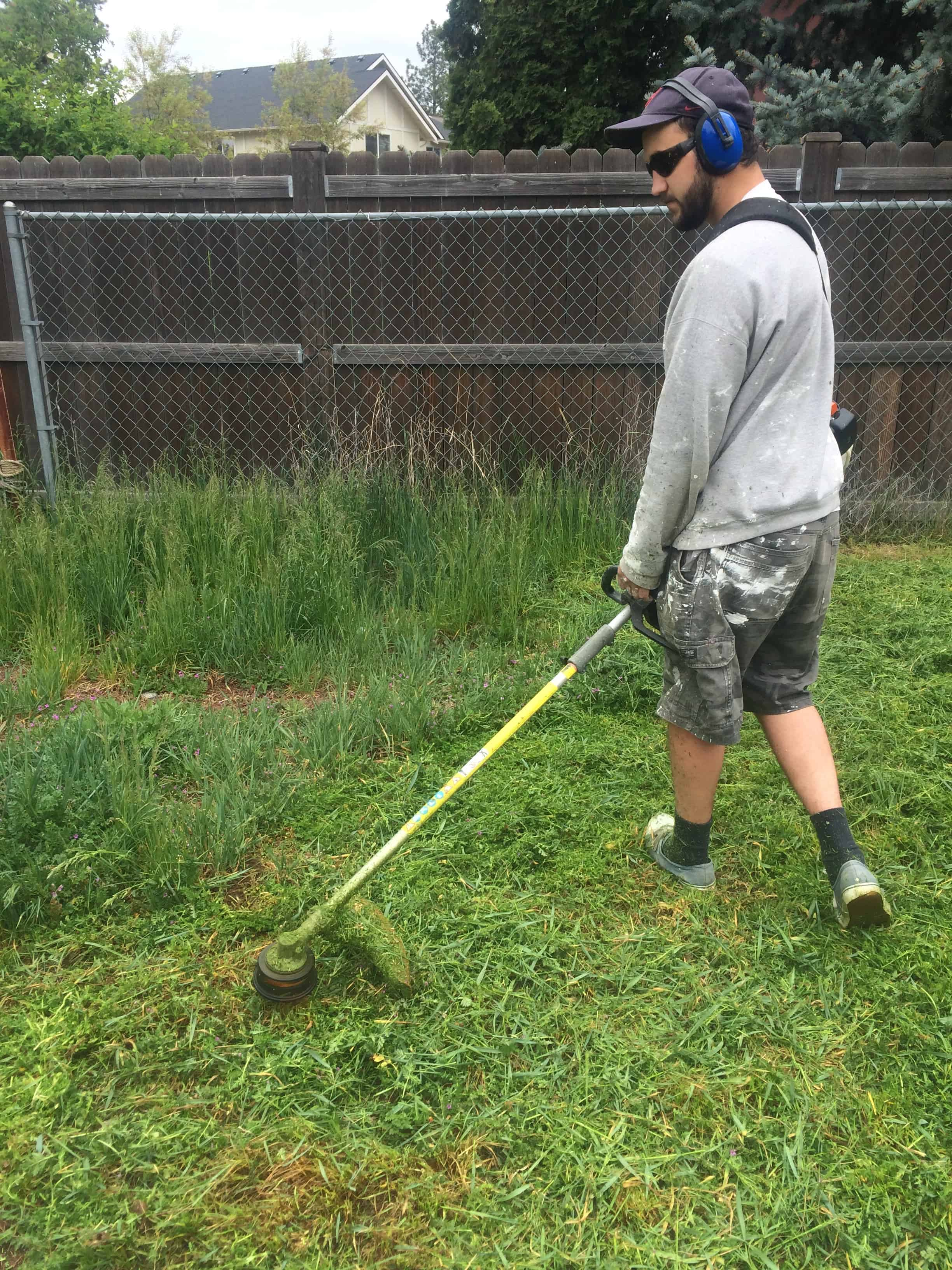 Man using weed wacker in backyard