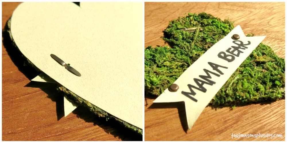 metal tags hold the name badge onto the moss heart for this adorable rustic baby shower name tag