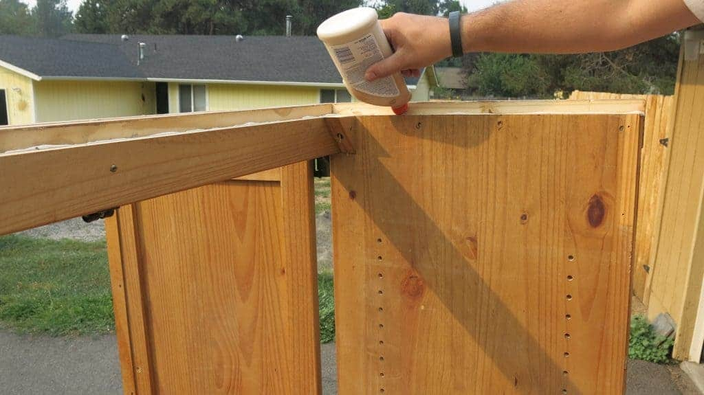 Man's hand adding wood glue to the top of entertainment center to turn into a DIY pantry