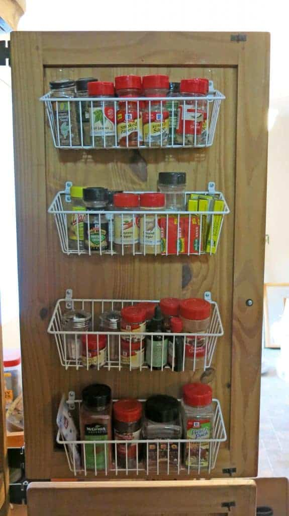 Open door on cabinet turned into a pnatry with white wire baskets attached to door filled with spices