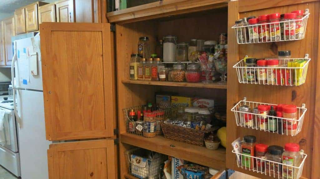 Entertainment Center converted to Pantry with wire shelving and wire baskets on the inside of the door filled with spices