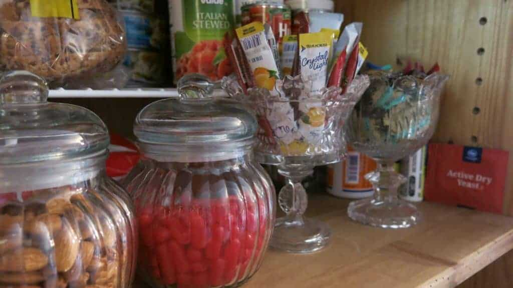 Glass jars for pantry organization filled with Hot Tamales, almonds and packets of lemonade