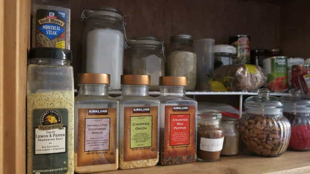 Pantry organization with spices lined up in front of food stacked on wire shelves