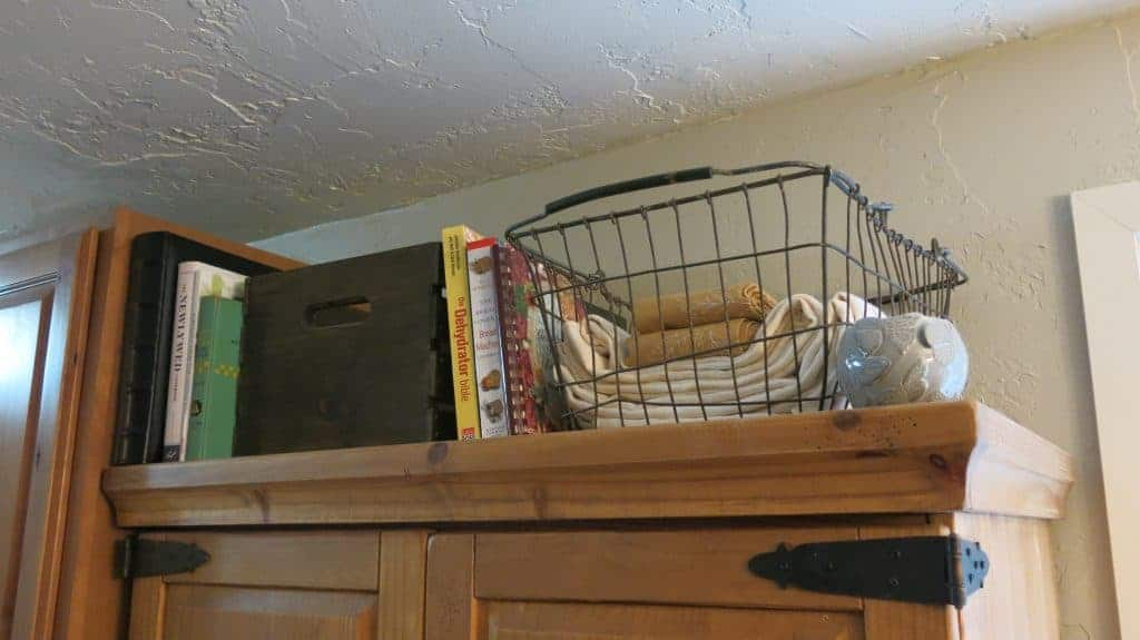 Top of DIY pantry with antique wire basket full of table cloths and cook books stacked on top of cabinet