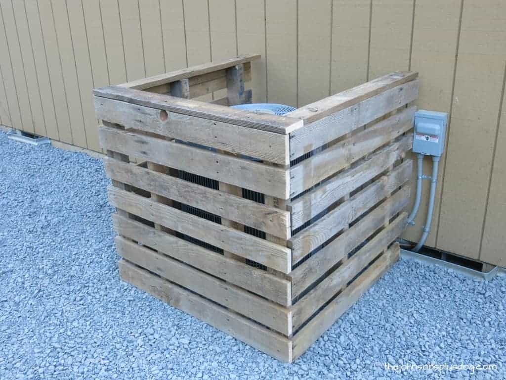 Air conditioning unit on side of house with a cover made from wood pallets