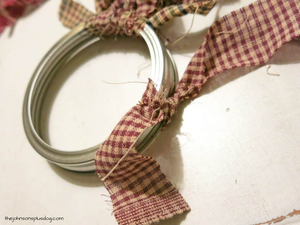 Strips of fabric being tied to a mason jar ring to create a fabric Christmas ornament