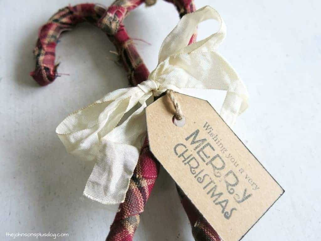 DIY fabric wrapped plastic candy canes form Dollar tree tied together to create DIY fabric christmas ornnaments with rustic style
