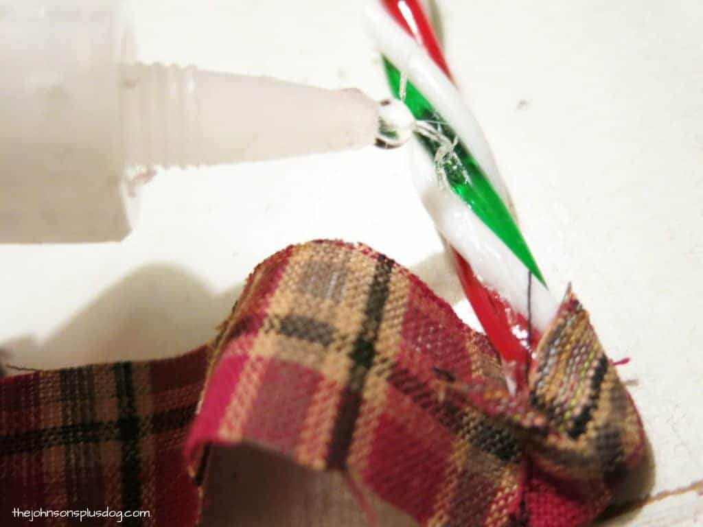 Glue being applied to plastic candy cane before wrapping fabric around it to make a rustic fabric christmas ornament for Christmas tree