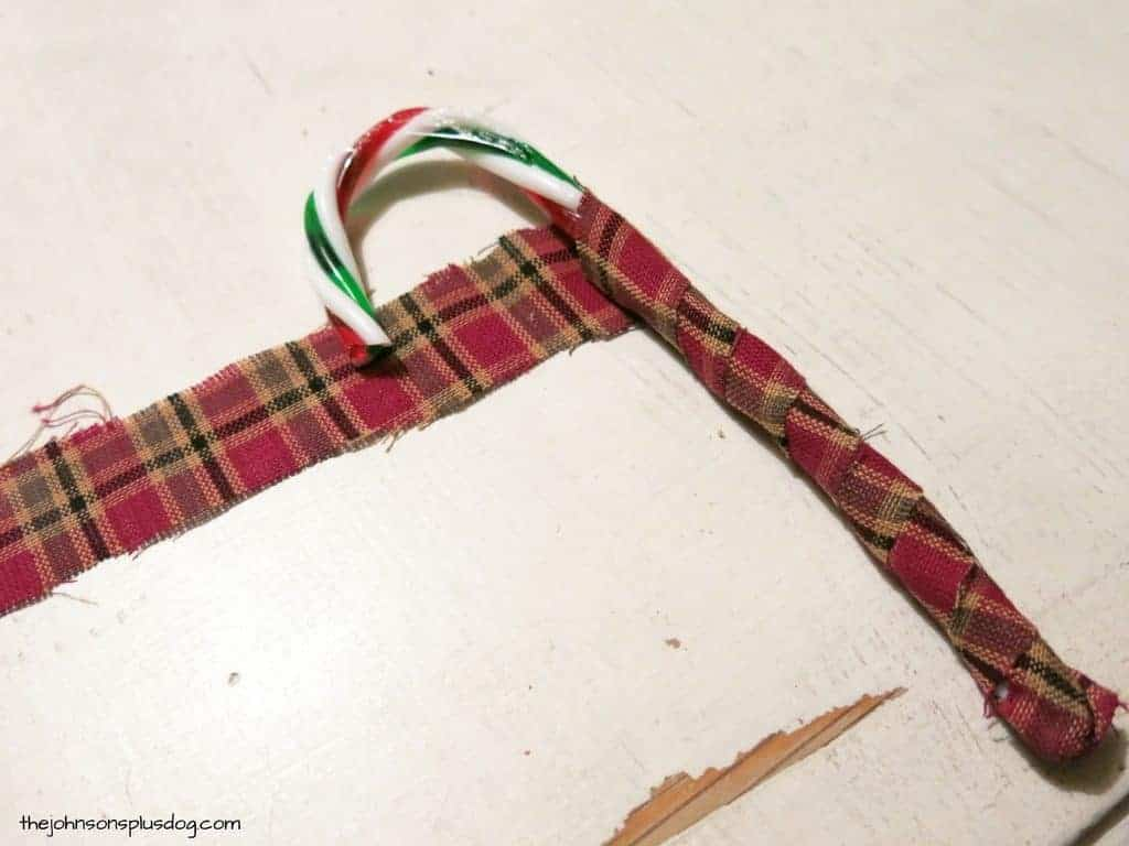 Strip of plaid homespun fabric being wrapped around a plastic candy cane to create fabric christmas ornaments