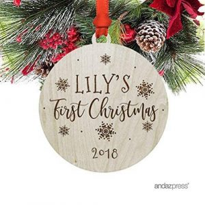 Baby's first christmas ornament printed on wood round ornament hanging from Christmas tree