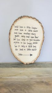 Rustic woodland sign with poem written on it for a nursery leaning on a gray wall on wood shelf