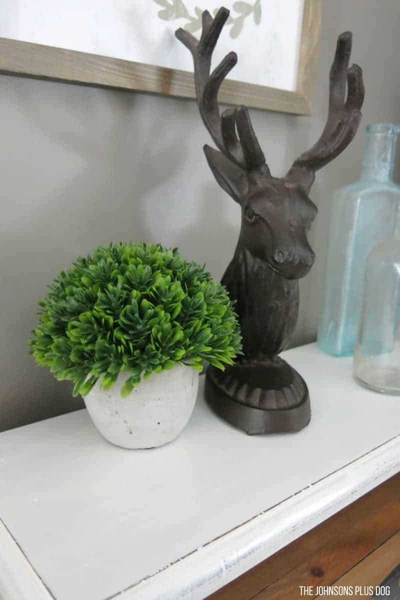 Mini faux boxwood plant in concrete planter sitting next to metal deer head and vintage bottles on top of white painted bread box in kitchen