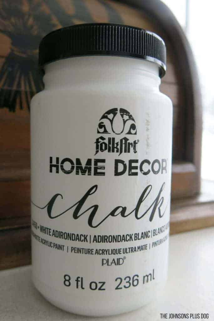 Bottle of Folk Art Home Decor Chalk Paint in White Adirondack sitting on table in front of vintage bread box
