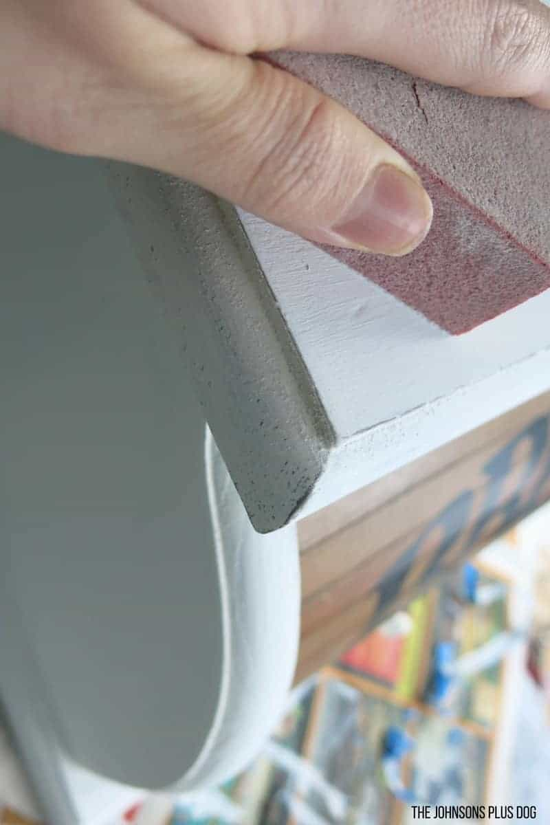 Hand using sanding block to distress a chalk painted vintage bread box