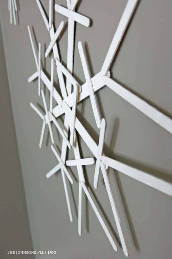 Side view of popsicle sticks snowflake attached to the gray wall