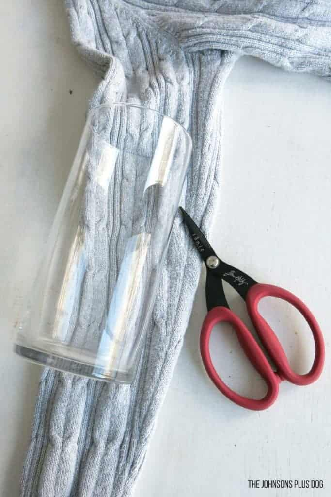 shows a clear glass vase laying down on a gray sweater material with scissors