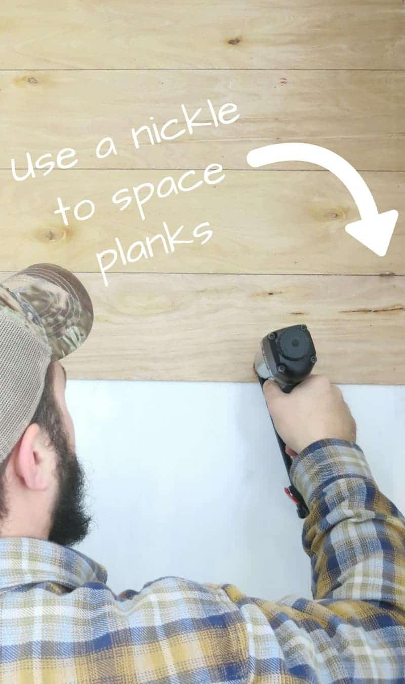 Man nailing wood planks to wall with nail gun with text overlay that says use a nickle to space planks