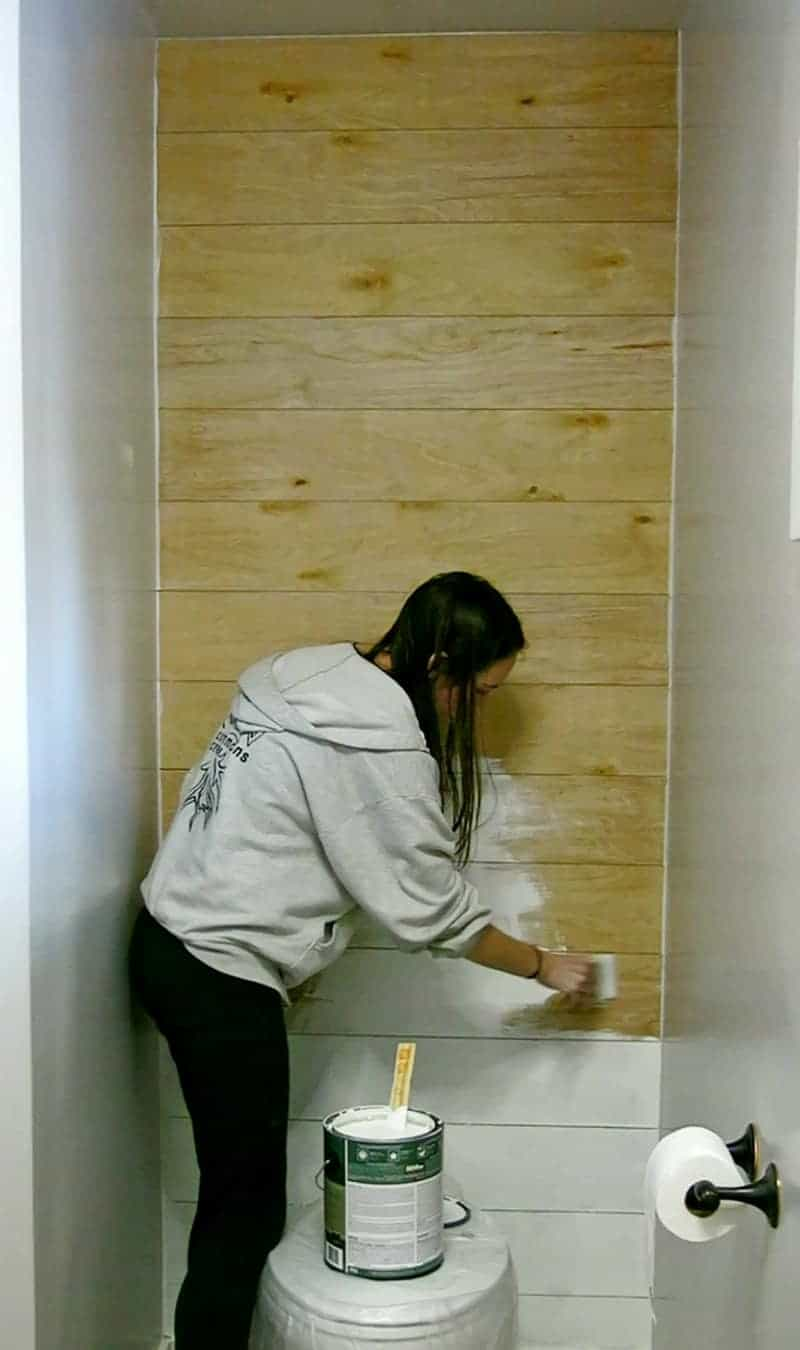 Woman painting wood planked wall with white paint to create a faux shiplap look