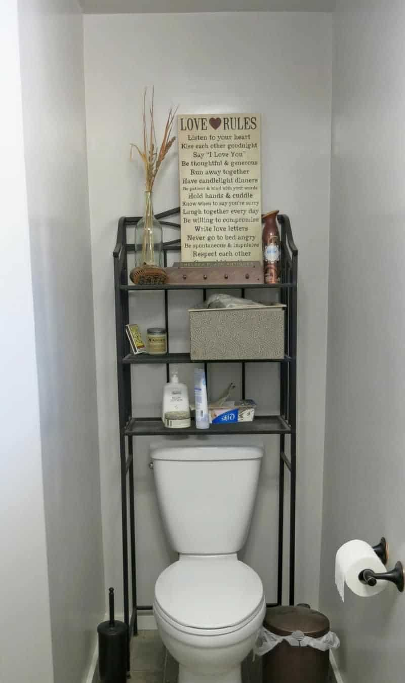 Photo of toilet with dark wire shelving unit over the toilet. Shelves above toilet are full of clutter and mess.