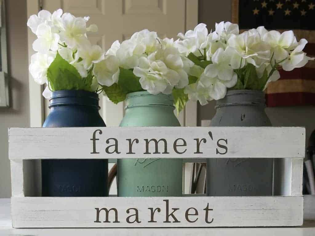 White crate with painted letters that say farmer's market and painted mason jars inside crate with white faux hydrangeas in them