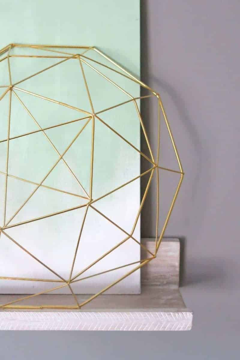 Cropped gold geometric bowl, ombre mint green canvas on the whitewashed herringbone designed wall hang shelf