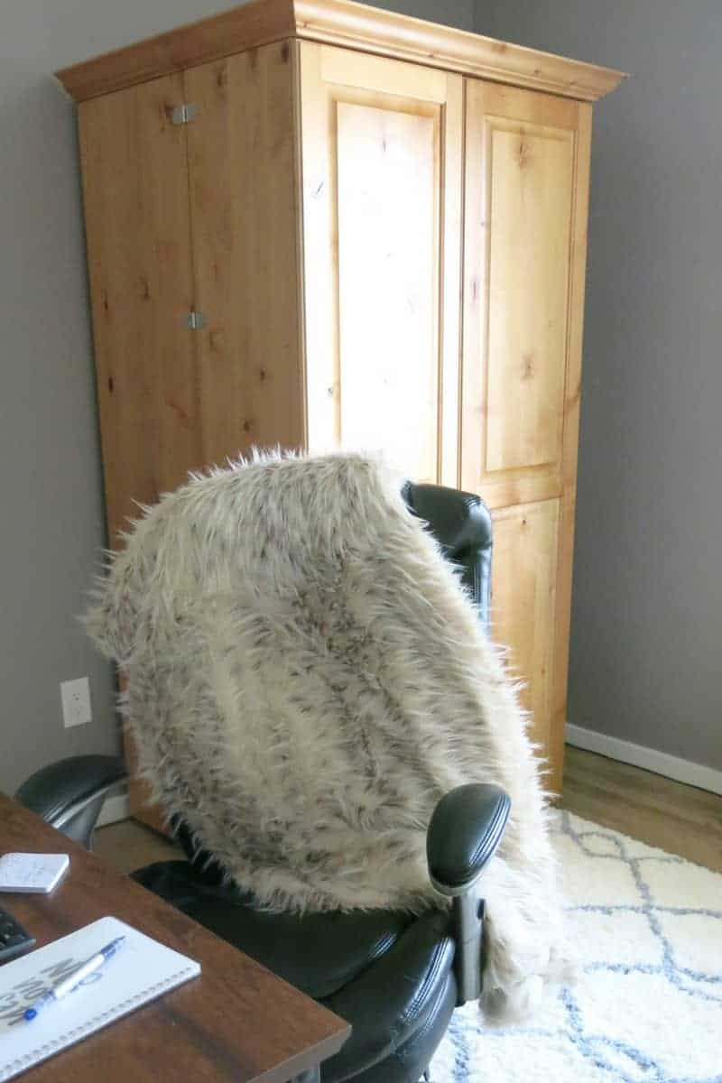 Fur throw on the office chair, ScrapBox and white rug.