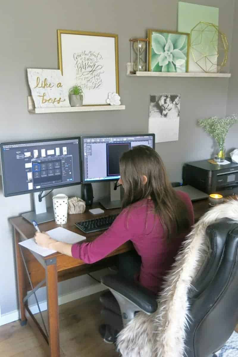 Woman working on the new marble and gold home office, 2 computer monitor, printer, and frames styled on the shelves