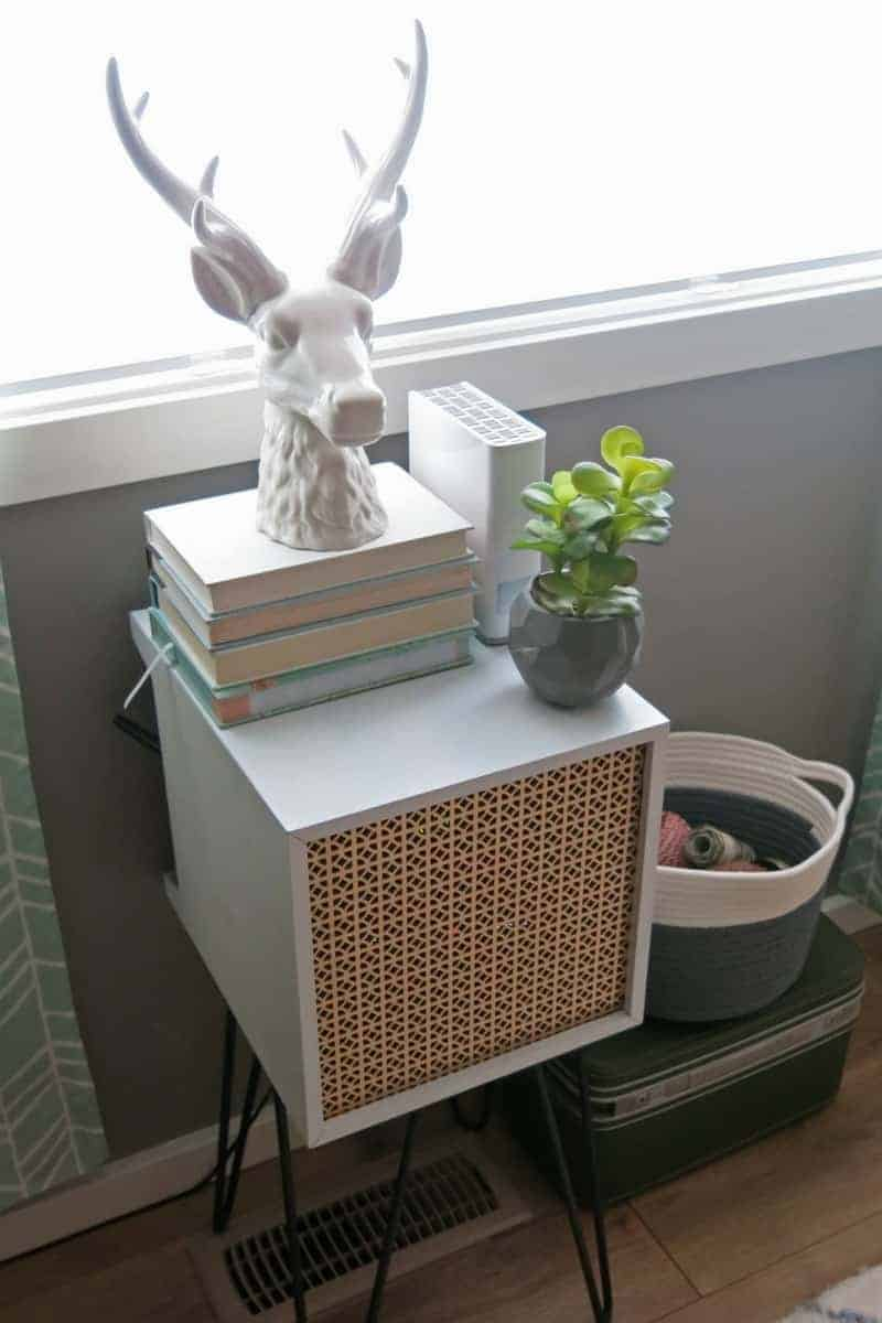 Mid-century side table, stag head, books, concrete geometric succulent planter, bin storage and a vintage suitcase