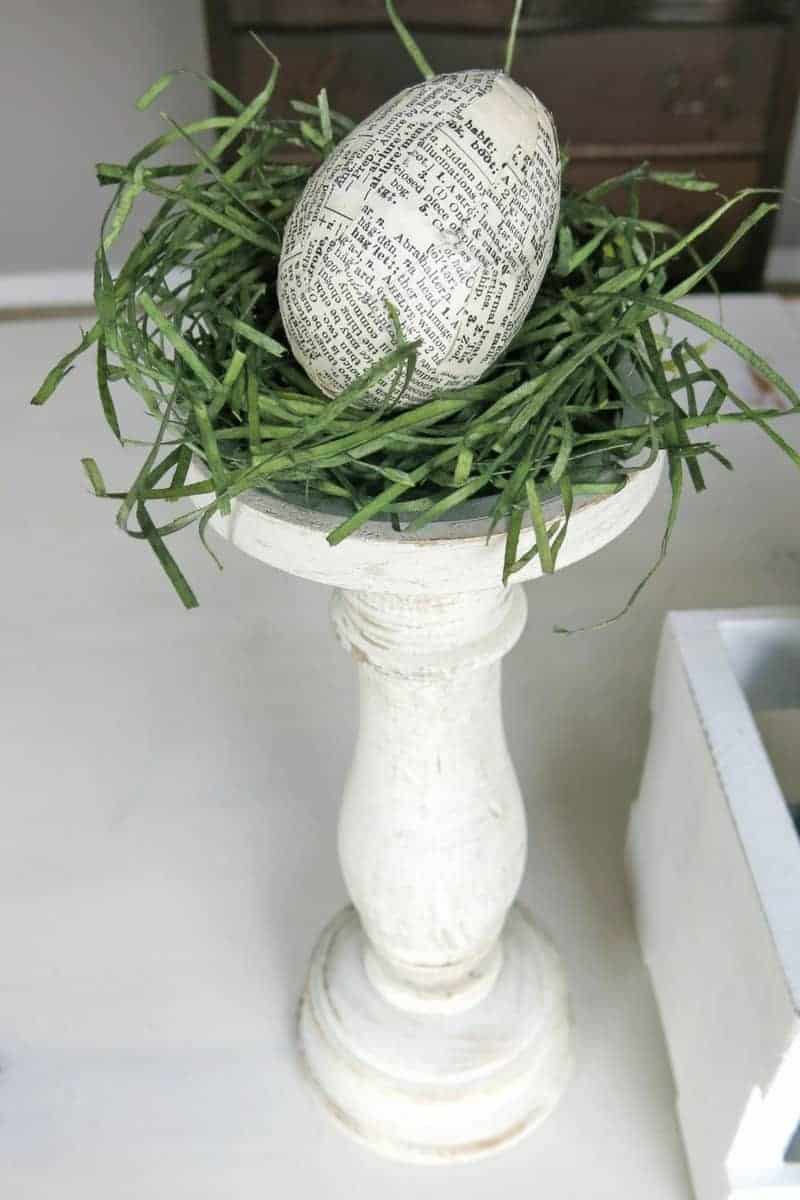 Vintage page covered Easter egg on mini nest at the top of farmhouse style candlestick