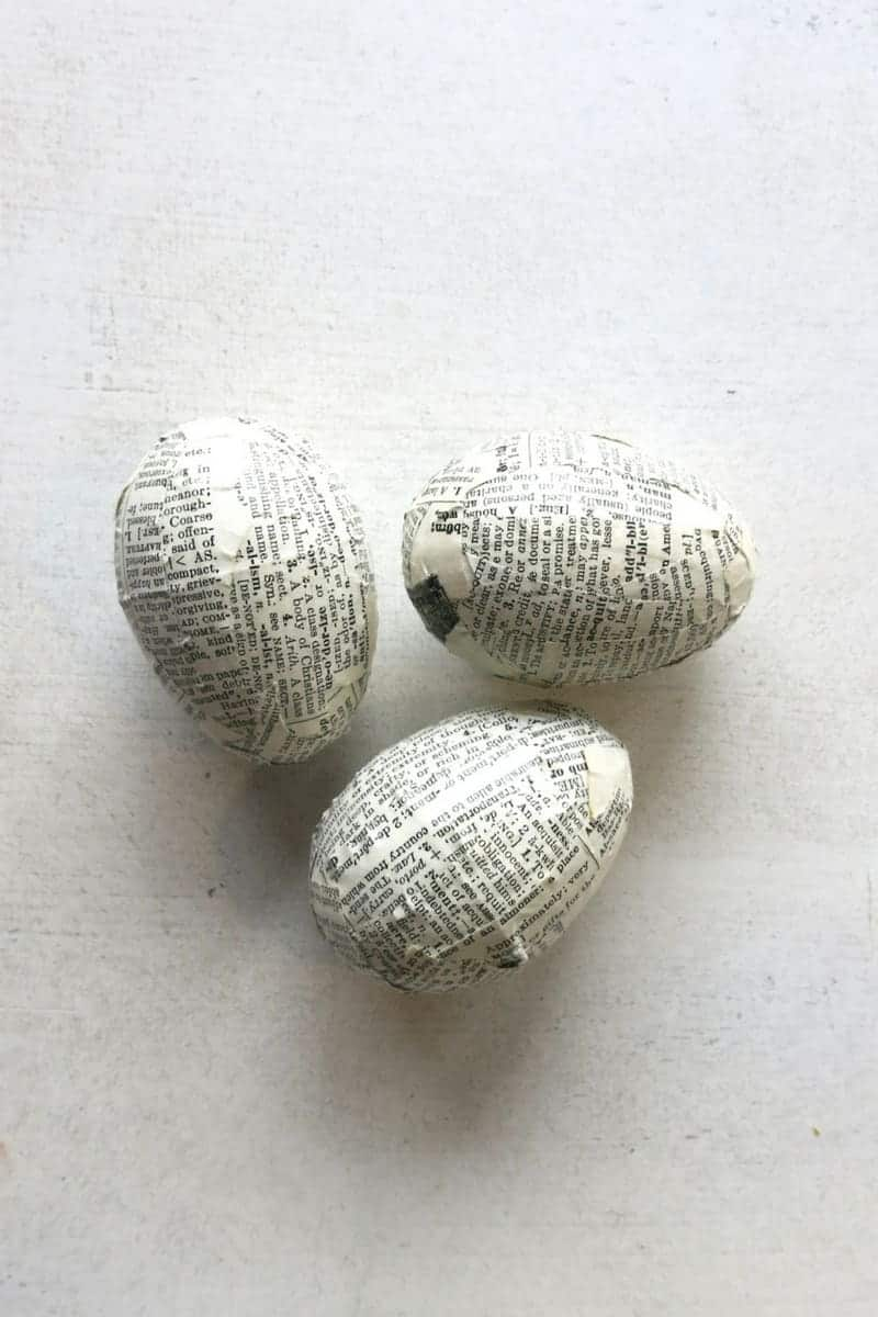 Three easter eggs sitting on white table background with covered in vintage pages so they have farmhouse style