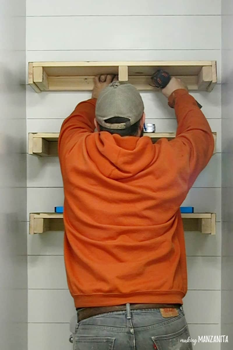 Man drilling in floating shelves to wall above toilet on faux shiplap wall