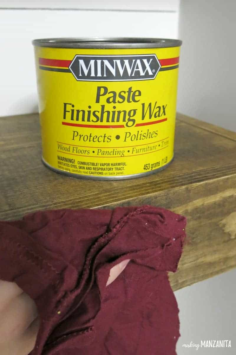 Can of Minwax Past Finishing Wax sitting on top of wooden floating shelf with hand applying the wax with a staining rag.