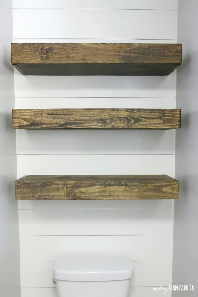 Three Dark Wood Stained Floating Wood Shelves Installed On A Faux Shiplap  Wall Above A Toilet