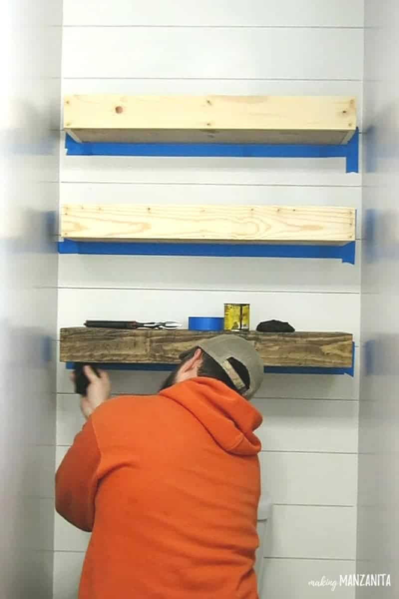 Man staining three floating shelves on wall with faux shiplap wall above toilet