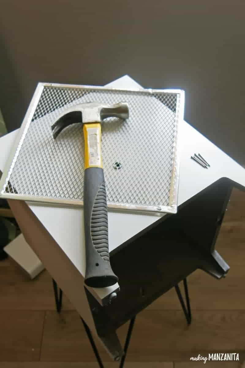 a hammer sitting on a wire grate, both sitting on top of a white box