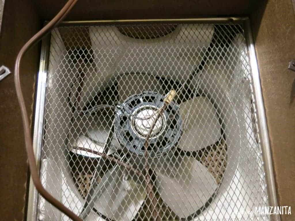 photo of a wire grate with a large fan underneath inside a box