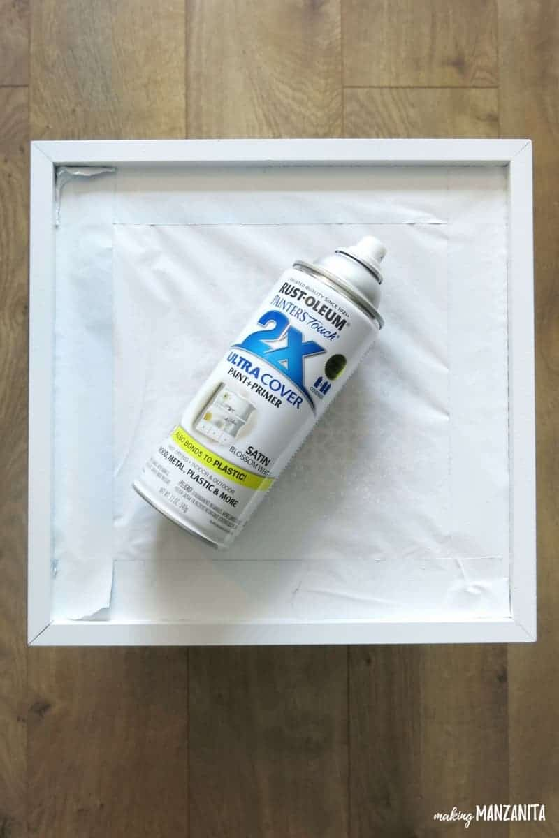 a can of spray paint primer is laying on a recently painted frame