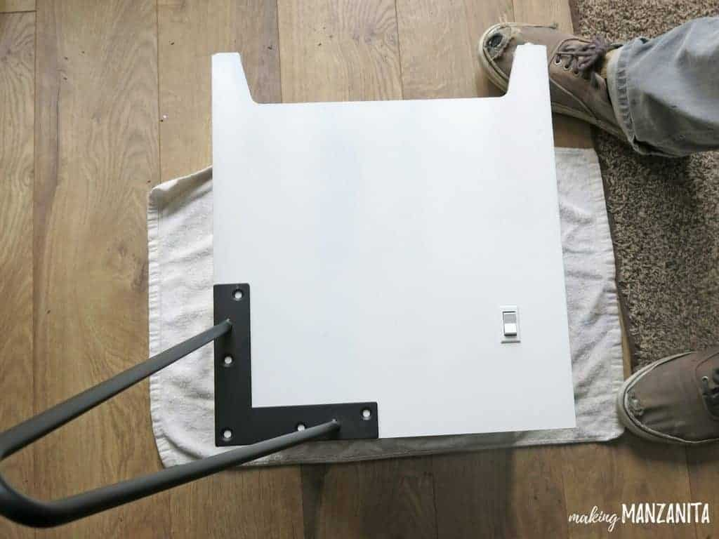 a white box laying on its side with a table leg ready to be attached