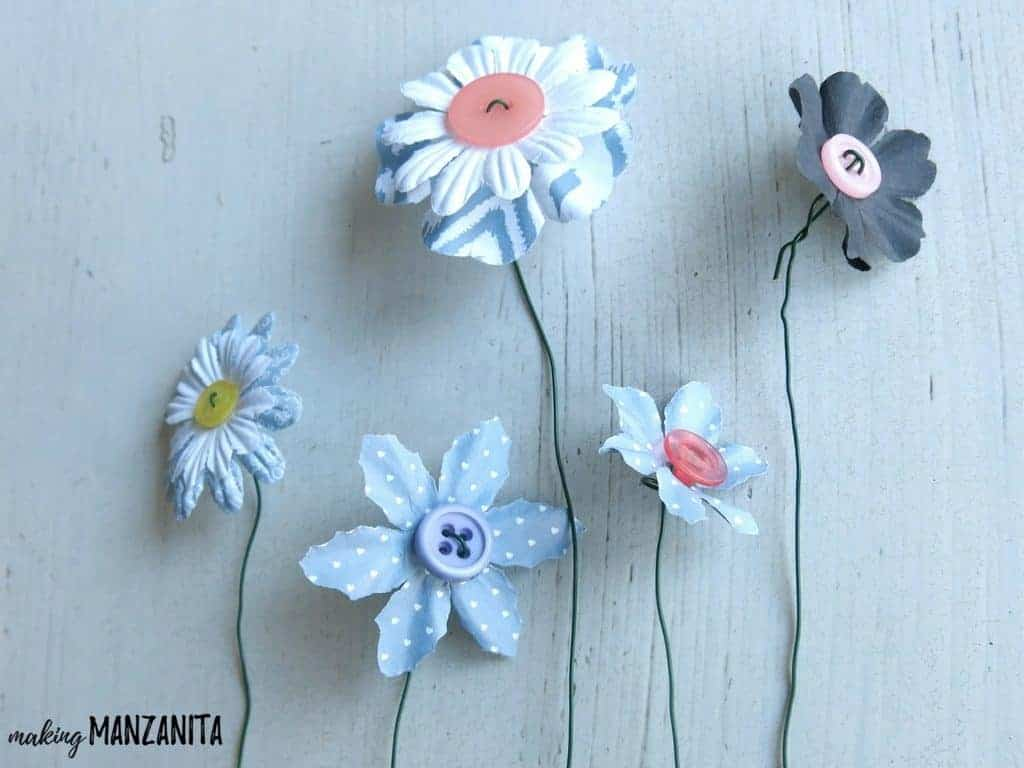 5 completed button flowers in different colors and sizes sitting on a white table