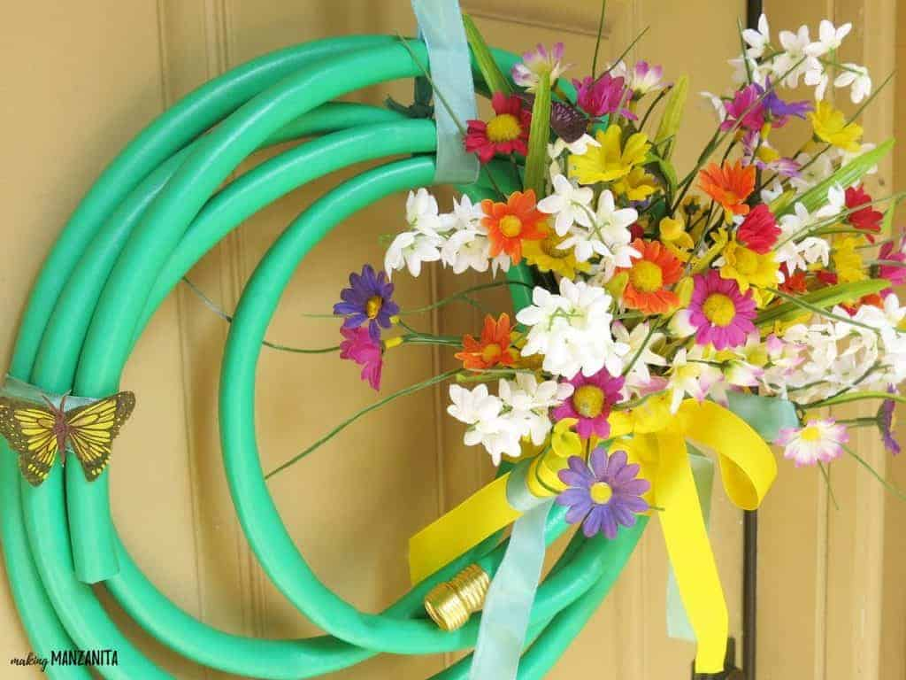 Wreath made with a green garden hose with colorful fake flowers and a yellow ribbon hanging on a door