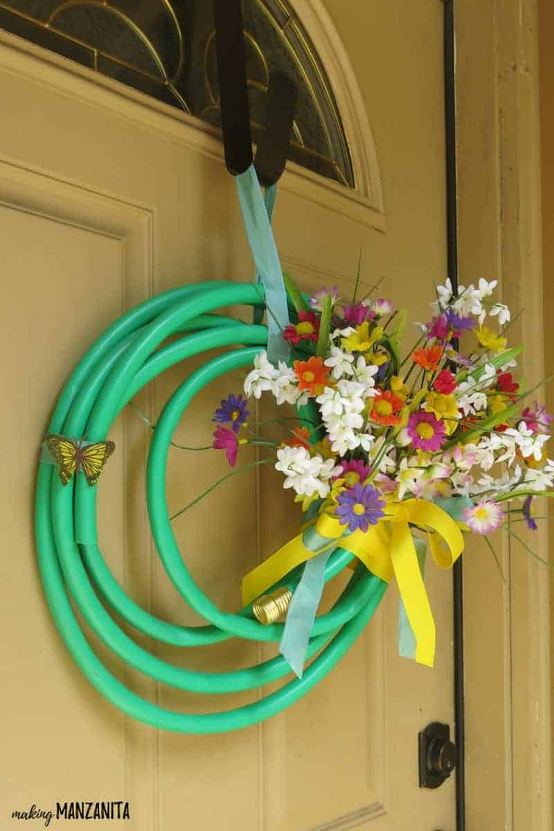 Summer wreath made with a garden hose, bright ribbon and colorful faux flowers hanging on a tan door