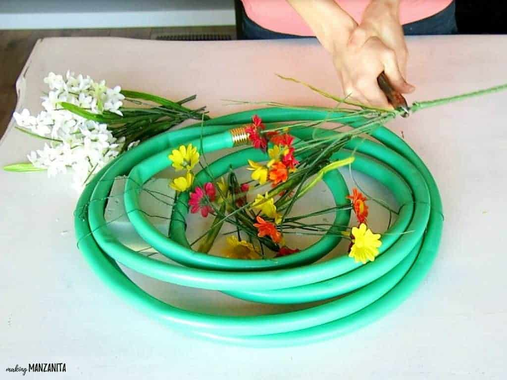 Clipping off fake flowers from stem to make a summer wreath from a garden hose