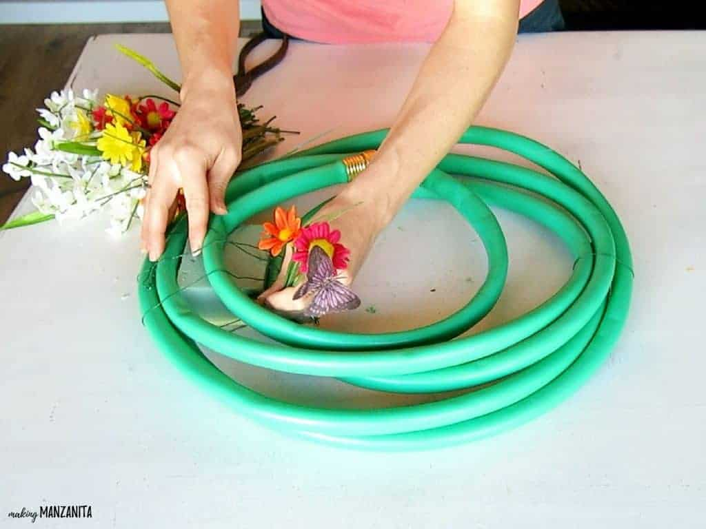 Attaching faux flowers into a foam block on a summer wreath made with a garden hose