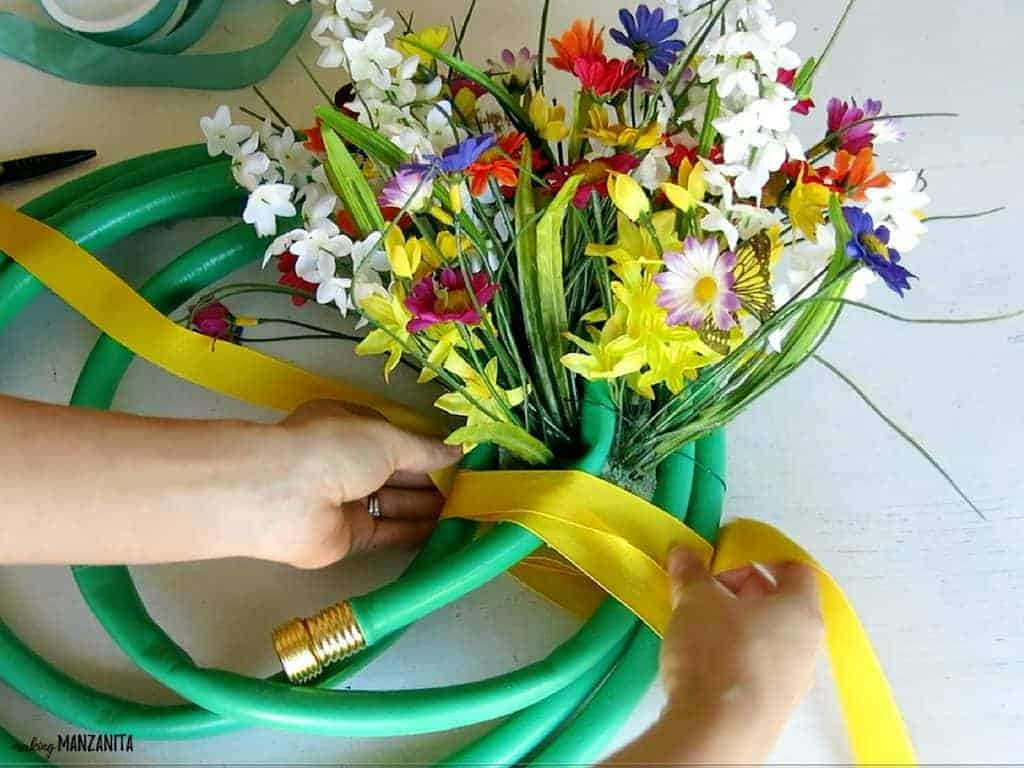 Wrapping yellow ribbon around the base of the foam block in a garden house wreath with faux flowers