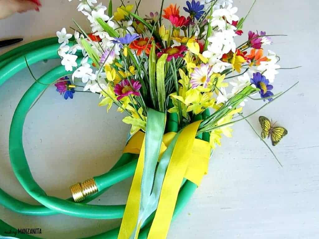 Wrapping ribbon around a summer wreath with made with a garden hose and foam block with faux flower arrangement