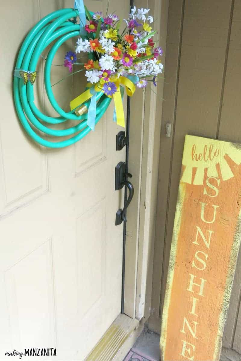 Garden hose wreath with fake flowers and ribbons hanging on a wreath hook with a tan door & hello sunshine wood sign in the background